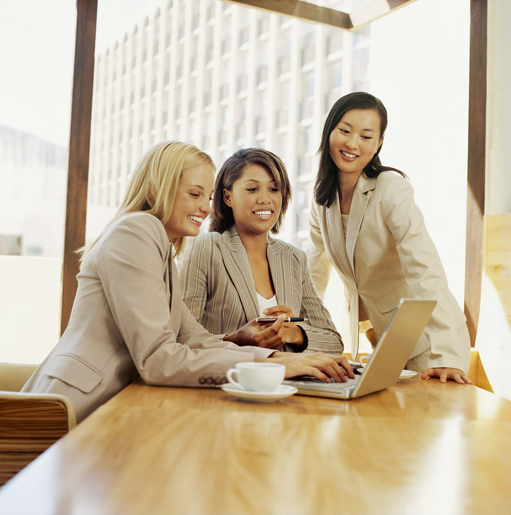 Close-up Of Three Businesswomen Discussing Work In Front Of A Laptop In An Office